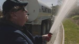 Michael Moore en action avec l'eau polluée de Flint. DR
